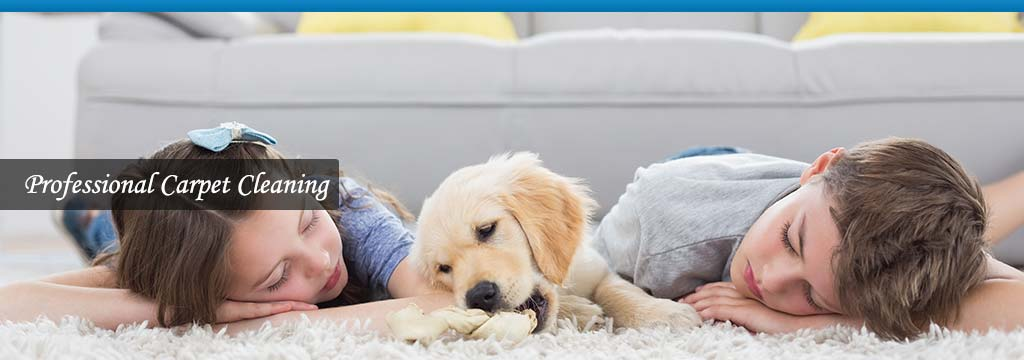 children and a puppy relaxing on a clean carpet